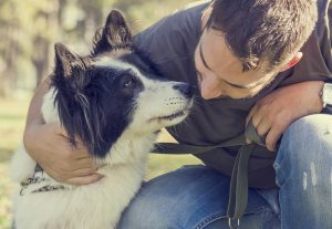 Man and dog on the leash hugging